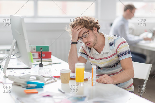 Tired young man working in creative office