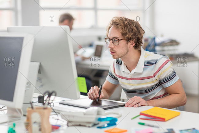 Young man working on computer and using tablet in creative office