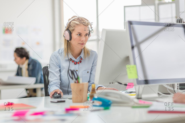 Young woman working on computer and wearing headphones in creative office