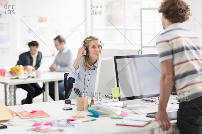 Young man looking at woman over monitor in creative office