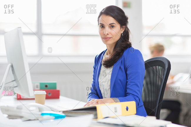 Mid adult businesswoman at desk in office