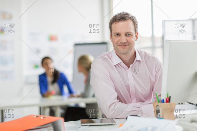 Mature businessman working at desk in office, portrait