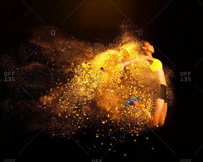 Young woman mid air emerging from yellow powder explosion
