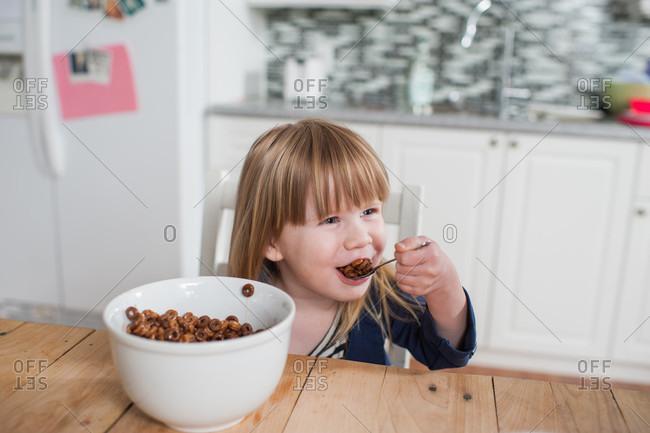 Girl eating bowl of cereal for breakfast