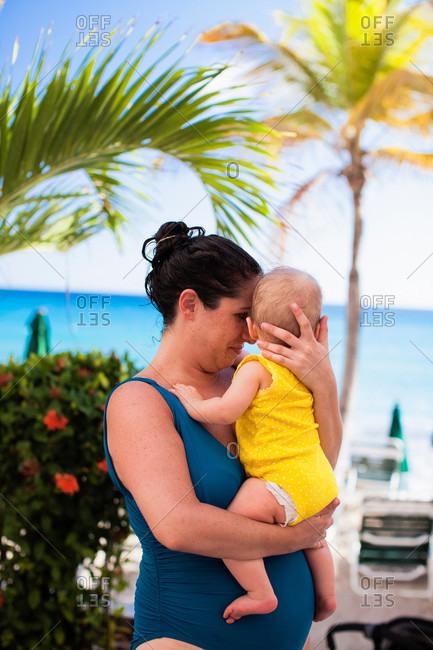 Mother in swimsuit holding baby daughter, St Maarten, Netherlands