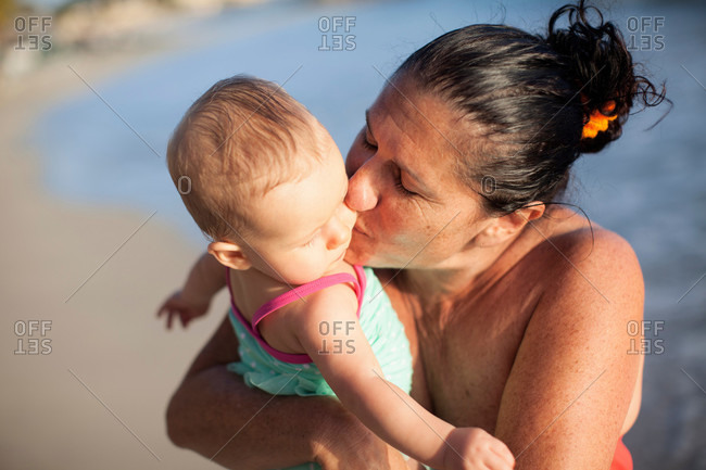Grandmother kissing baby granddaughter on cheek