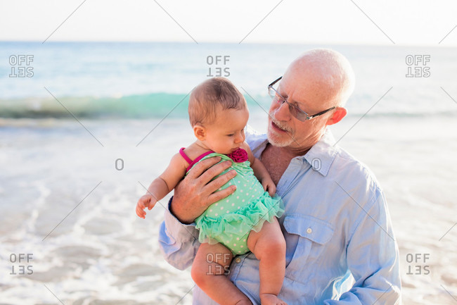 Grandfather holding granddaughter by sea, St Maarten, Netherlands