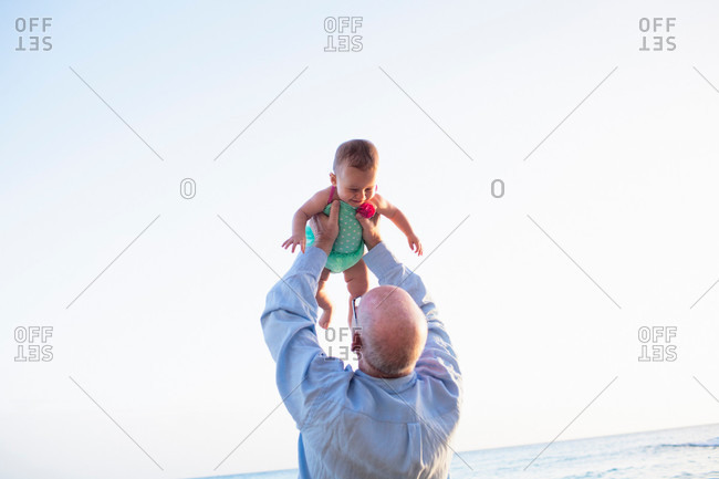 Grandfather lifting granddaughter above head, St Maarten, Netherlands