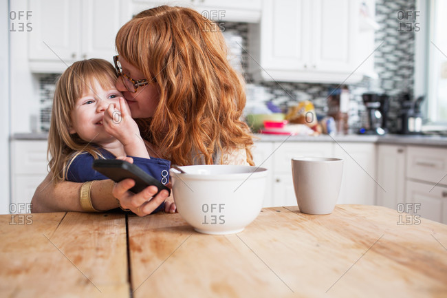 Mother and daughter hugging at breakfast table