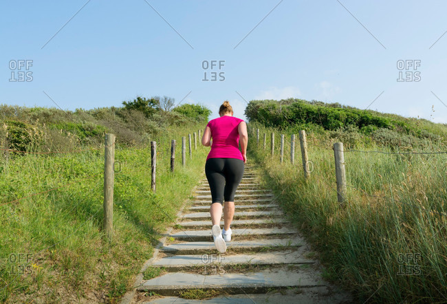 Rear view of woman running up stairs