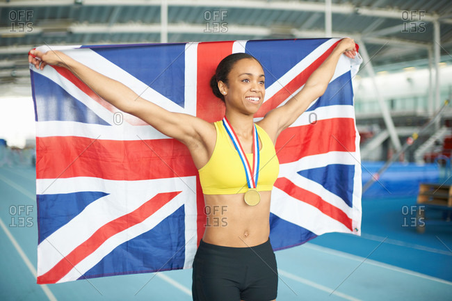 Young female athlete holding UK flag with gold medal