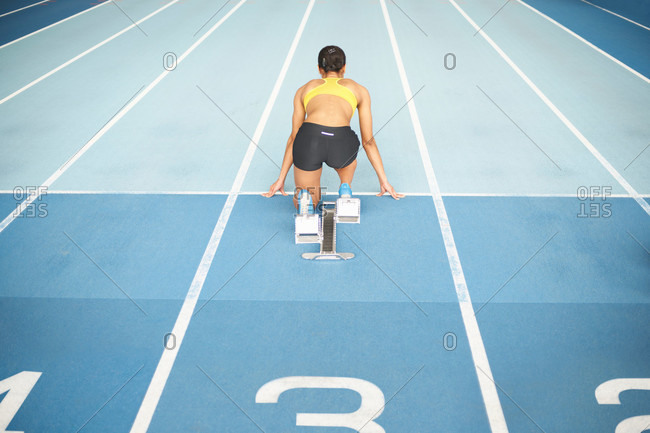 Young female athlete on starting blocks, rear view