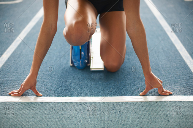 Young female athlete on starting blocks, close up
