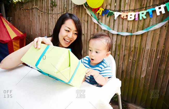 Mother giving baby boy a birthday present