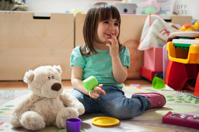 Girl playing with toy tea set