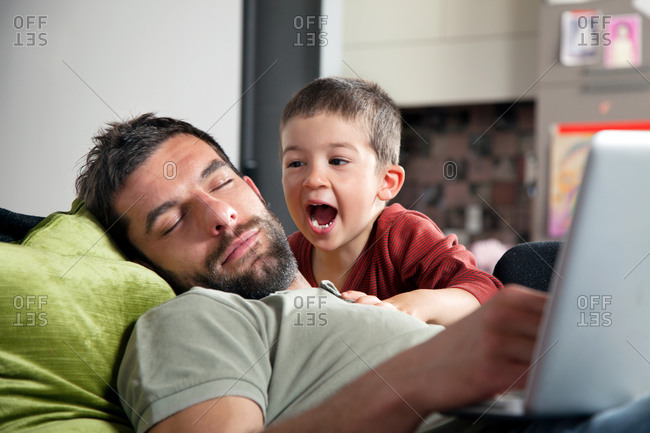 Father asleep on sofa with son shouting