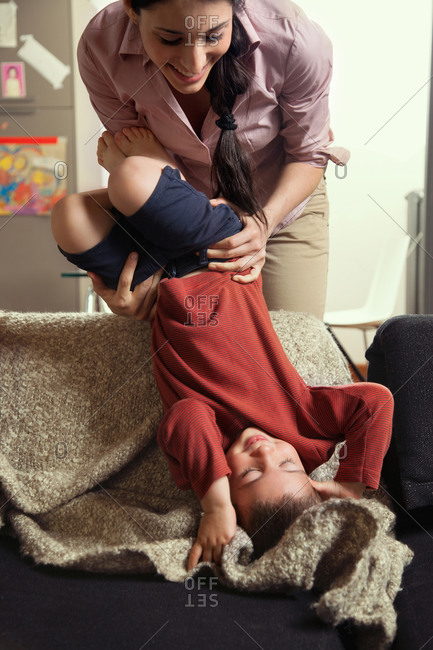 Mother holding son upside down