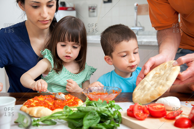 Family making homemade pizza together