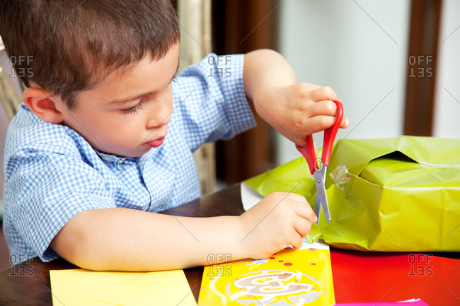 Boy cutting wrapping paper with scissors