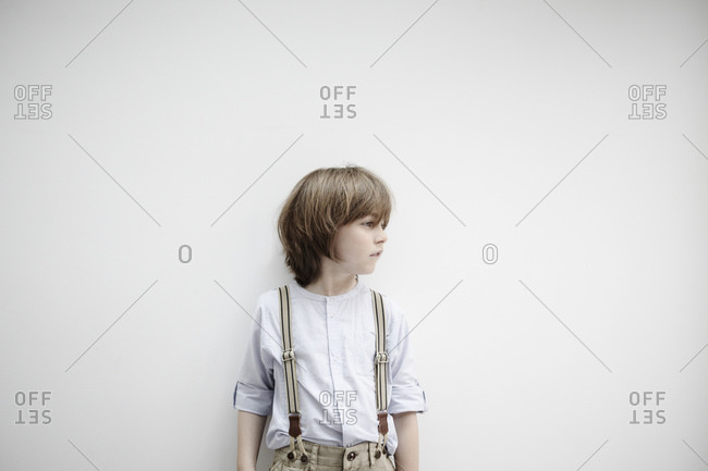 Boy standing against white wall