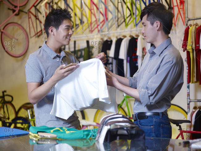 Two young men looking at t-shirts in bike shop