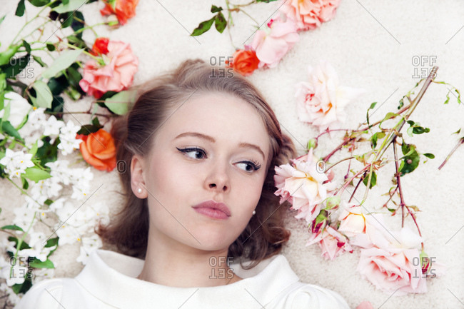 Young woman lying amongst roses
