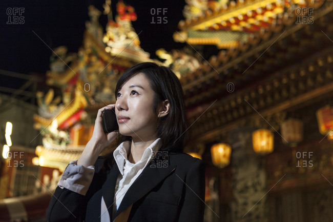 Businesswoman on cellular phone, night market, Taipei, Taiwan