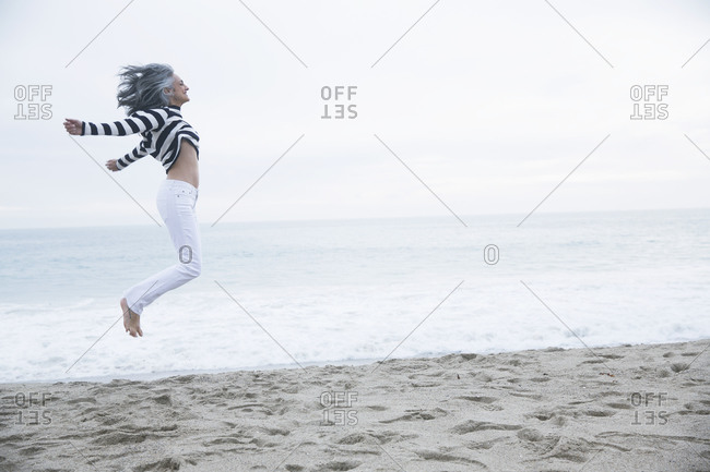 Mature woman jumping mid air on beach, Los Angeles, California, USA