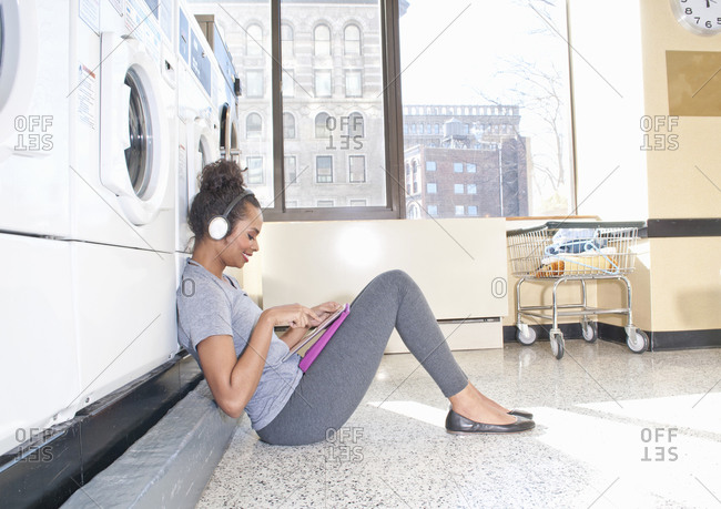 Young woman in launderette, wearing headphones, waiting for laundry to finish