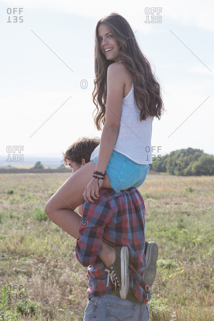 Young man carrying woman on shoulders