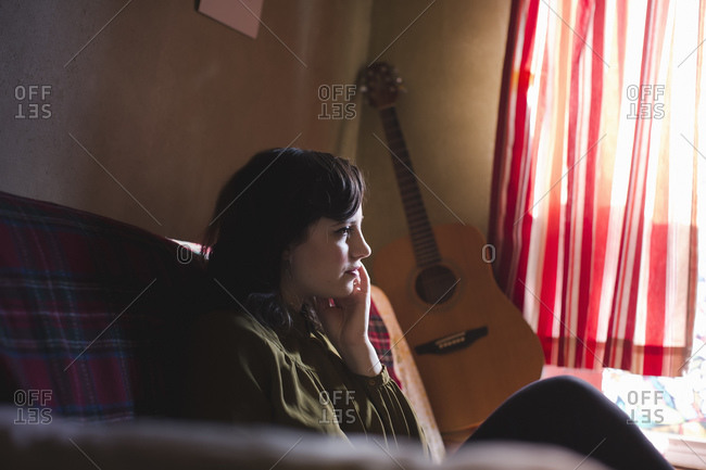 Young woman sitting on sofa, guitar in background