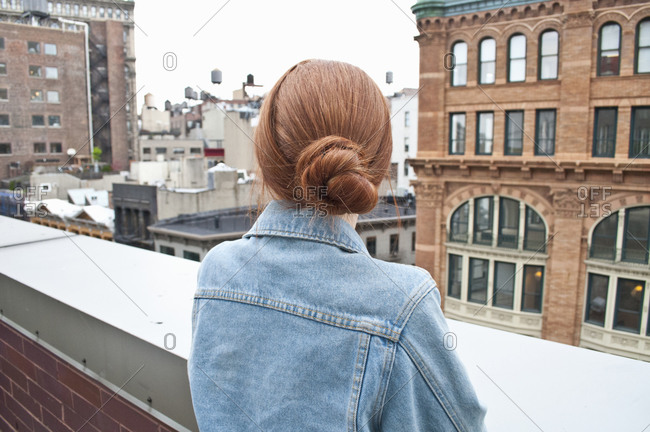 Young woman looking at city from rooftop