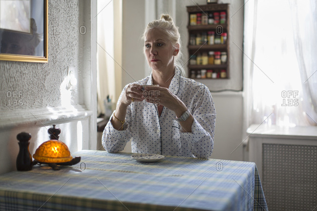 Mature woman sitting at breakfast table with teacup