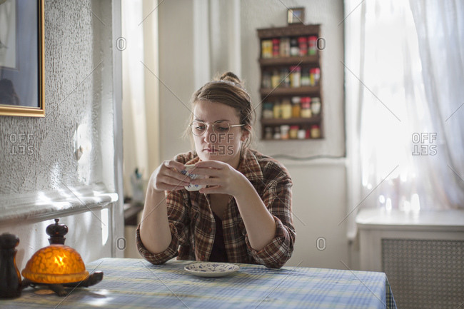 Portrait of young woman sitting at breakfast table looking down at teacup