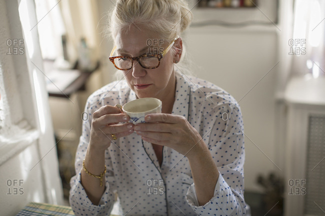 Sad mature woman sitting at breakfast table with teacup