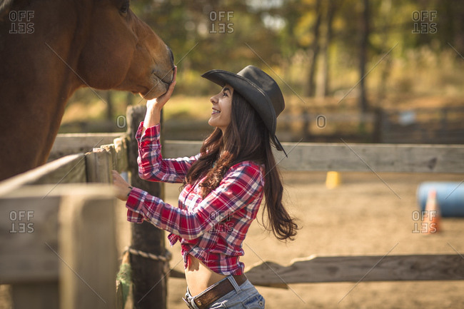 Cowgirl showing affection to horse on ranch