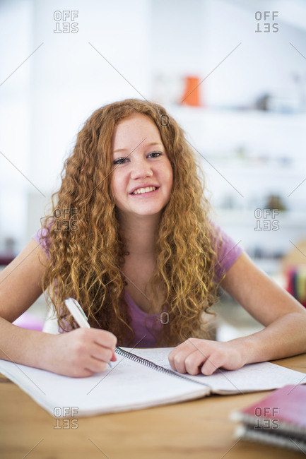 Teenage girl writing notes in class