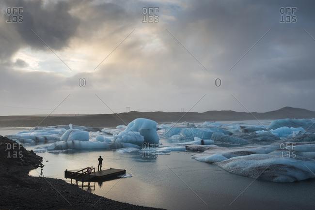 Tourist photographing by blue icebergs, Jokulsarlon Glacier Lagoon, Southeast Iceland