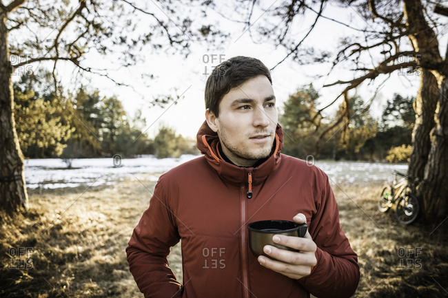 Young male hiker drinking coffee in lakeside forest