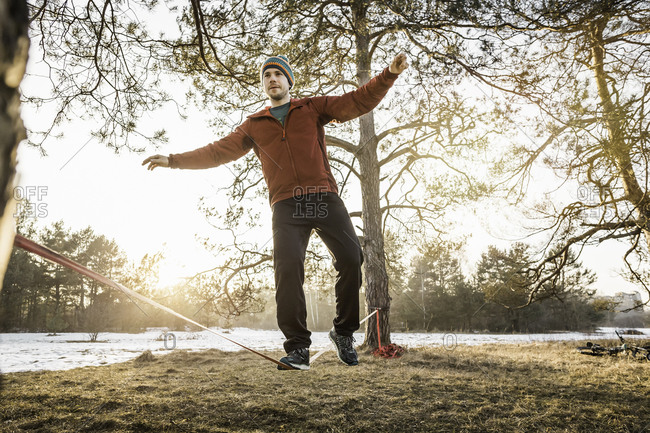 Young man practicing on slackline in lakeside forest