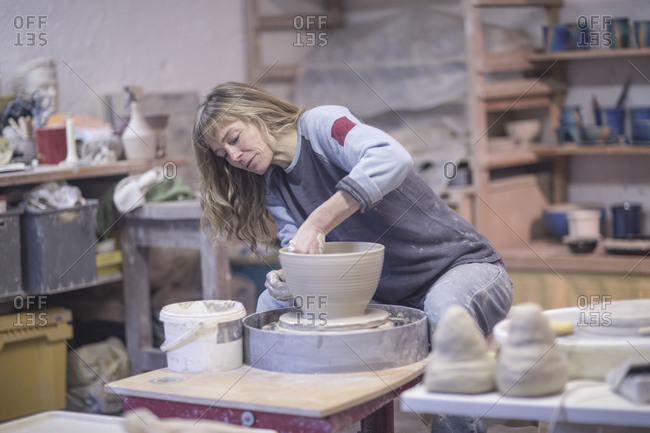 Female potter shaping clay pot on pottery wheel