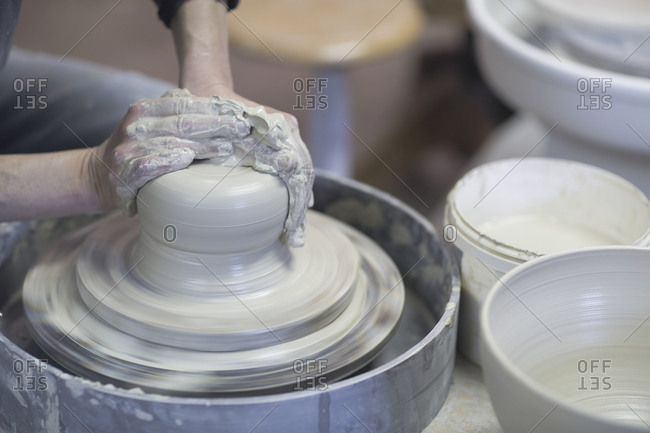 Close up of female potters hands forming clay on pottery wheel
