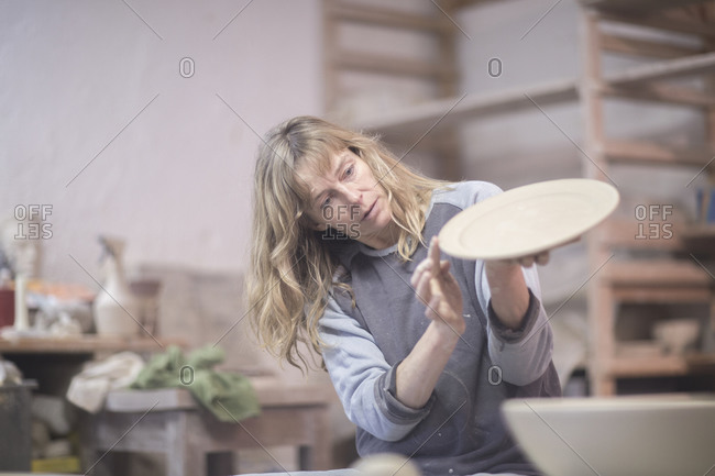 Female potter checking edge of plate in workshop