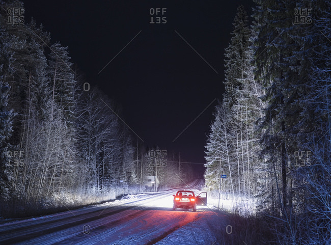 Stationary car with open door on snowy, rural road, at night