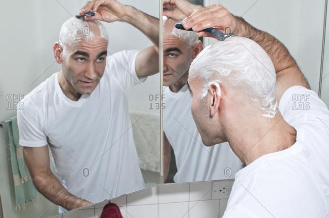 Young bald man shaving head in bathroom mirror