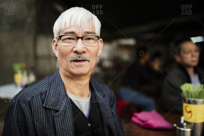 Portrait of senior man with grey hair wearing glasses looking at camera