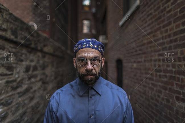 Portrait of mature man wearing taqiyah and glasses in alley looking at camera