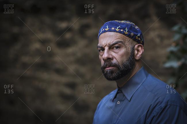 Portrait of mature man wearing taqiyah, looking at camera scowling
