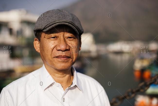Portrait of senior man wearing white shirt and flat cap, looking at camera smiling