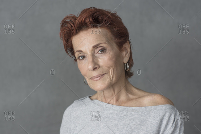 Studio portrait of beautiful mature woman with short red hair